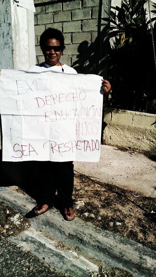 , En Barahona, Madre de alumnos protesta frente a escuela exigiendo respeto a derechos educativos.