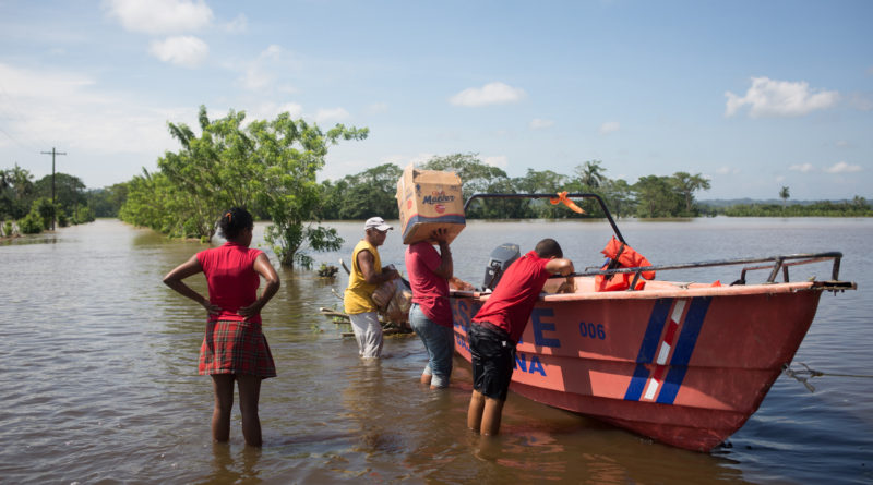Neighbors transport drink and food in a boat of Civil Defense for the people who remain incommunicado by the flood of the River Yuna. The Yuna River overflows for kilometers and causes floods that cause to lose crops of banana, rice and pumkin and leave incommunicado to the communities of Acicate Abajo, La Raya, La Isleta, Cerrejón, El Paso de la Barca among others communities Duarte province. Huracán María, Dominican Republic